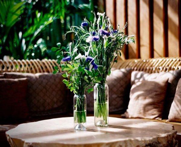 Deux vases transparent en forme de q de bouteilles posés sur une table avec une jolie composition florale pour le petit je ne sais quoi