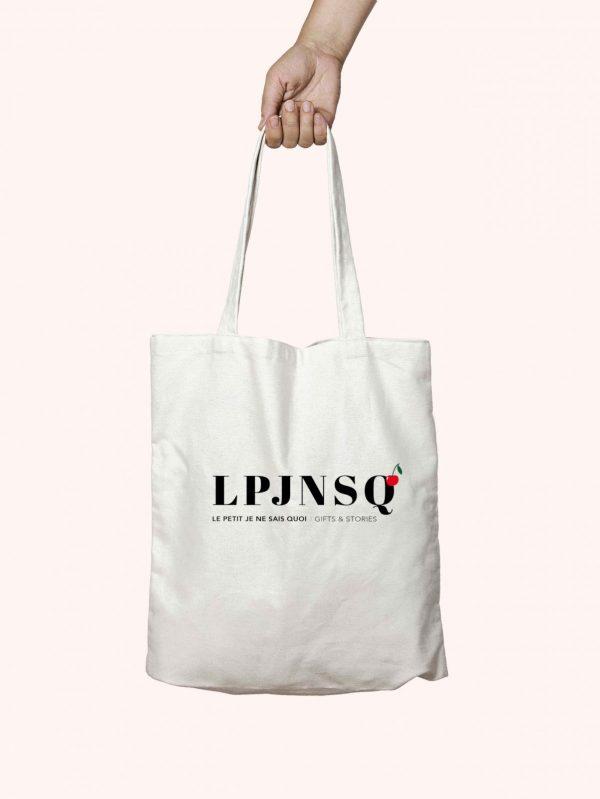 Tote bag sac fourre tout de couleur écru sur lequel est inscrit LPJNSQ, les initiales de la marque Le petit je ne sais quoi, l'image est sur fond rose