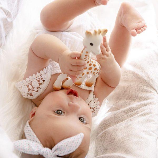 Un bébé a dans sa main le jouet français en caoutchoux sophie la girafe pour le petit je ne sais quoi