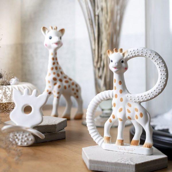 Trois produits de la marque sophie la girafe posés sur une commode en bois pour le petit je ne sais quoi