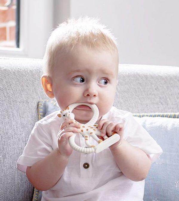 Un enfant assis machouille l'anneau de dentition sophie la girafe pour le petit je ne sais quoi