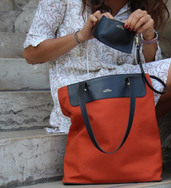 Photo d'une femme assise sur marche escalier avec un sac en lin de couleur brique le petit je ne sais quoi