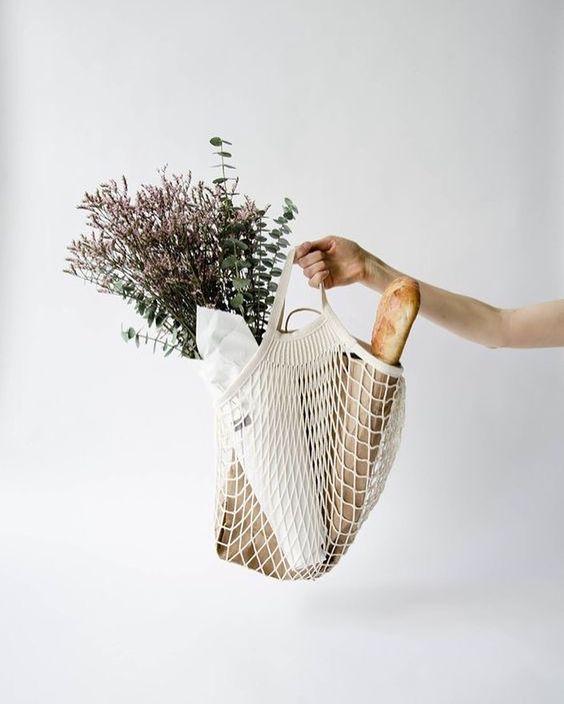 Un bras tient à la main un sac filet avec du pain dedans et des fleurs pour le petit je ne sais quoi