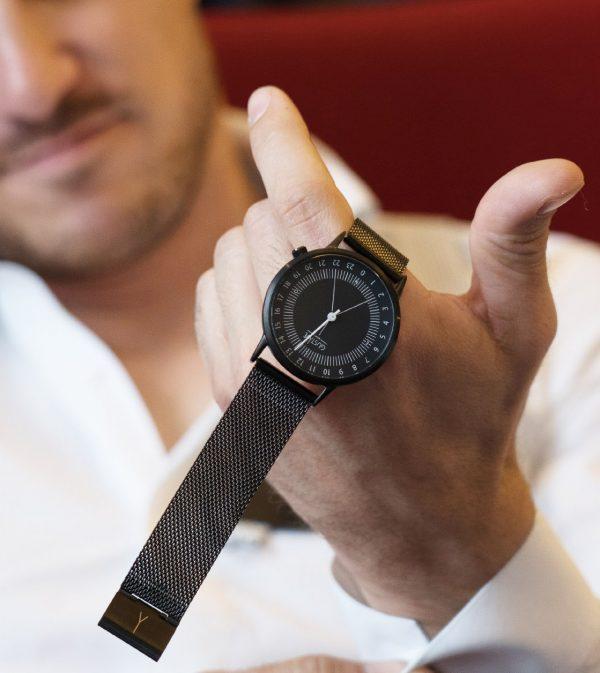 Homme en chemise blanche qui regarde une montre noire bracelet milanais noir et cadran noir, très sobre et élégante pour le petit je ne sais quoi