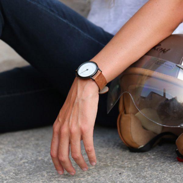 Femme assise sur le trottoir sa main est posée sur un casque de moto, elle porte une montre élégante en bracelet cuir marron et cadran blanc pour le petit je ne sais quoi