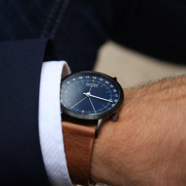 Main d'un homme qui porte une montre avec un cadran bleu et un bracelet en cuir marron pour le petit je ne sais quoi