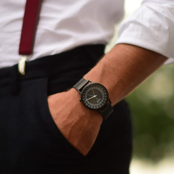 Homme en costume qui porte une chemise blanche et des bretelles, sa main est dans la poche et il porte une montre noire avec bracelet milanais noir et cadran noir, il est élégant pour le petit je ne sais quoi