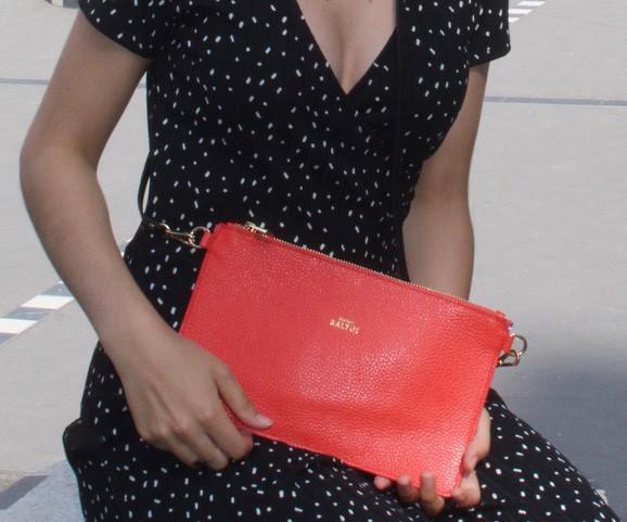 Femme en robe noire à petits pois qui porte une pochette rouge dans ses mains pour le petit je ne sais quoi