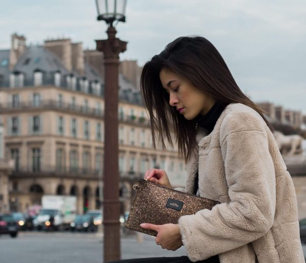 Femme avec un manteau beige a Paris qui porte une pochette en strass mordoré pour le petit je ne sais quoi