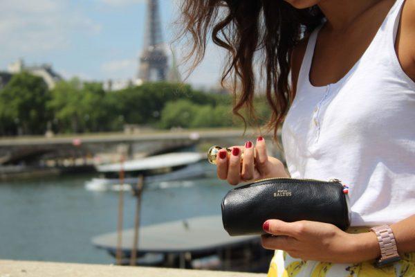 Une femme devant la tour eiffeil tient une trousse d'écolier pour ranger ses stylo, style vintage en cuir noir