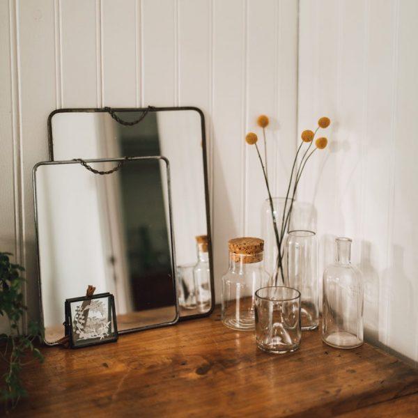 cul de bouteille upcyclés en vase transparents, les vases sont posées sur une table en bois avec un beau moroir de barbier
