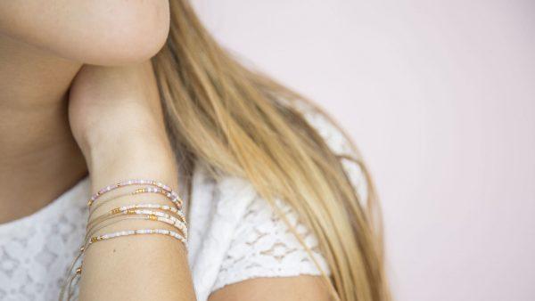 Une femme blonde porte plusieurs bracelets à son poignée pour le petit je ne sais quoi