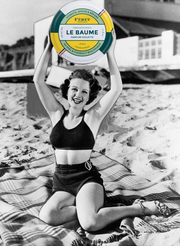 Une femme sur la plage a les mains en l'air et entre ses mains elle tient le baume à la violete de Féret Parfumeur pour le petit je ne sais quoi
