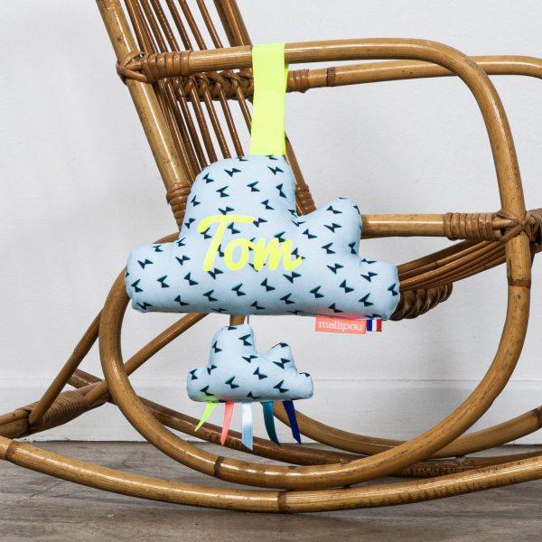 Une boite à musique de couleur bleue est accroché à un fauteuil en osier pour l petit je ne sais quoi