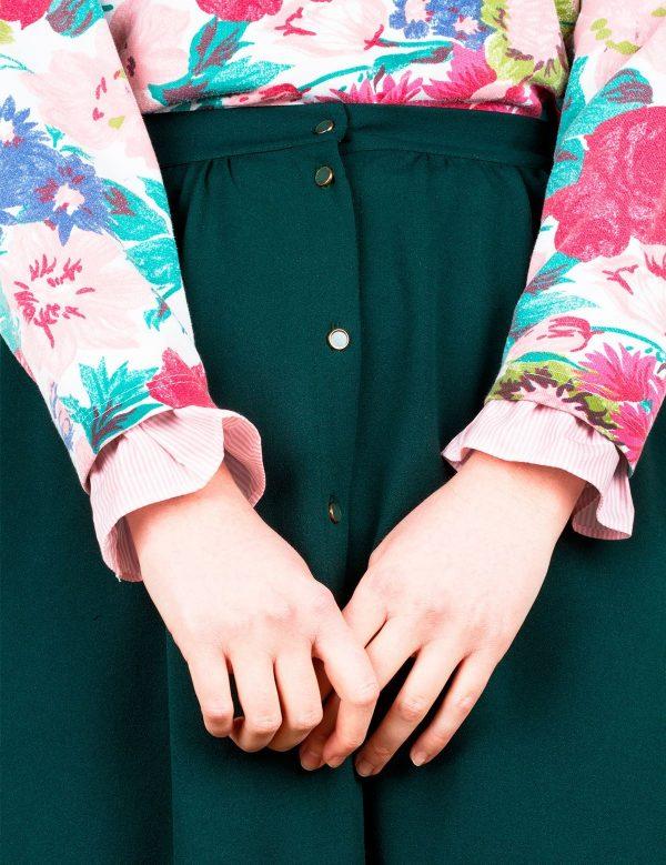 Une femme en jupe vert sapin et pull floral porte des manchettes en tissu à rayures roses claires pour le petit je ne sais quoi