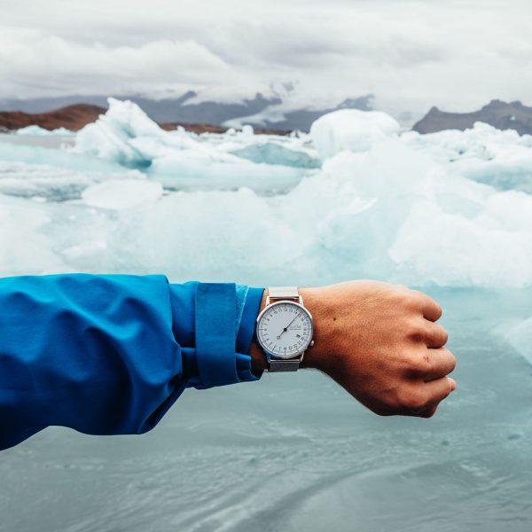 Homme devant un glacier qui montre sa montre avec un bracelet milanais argenté pour le petit je ne sais quoi