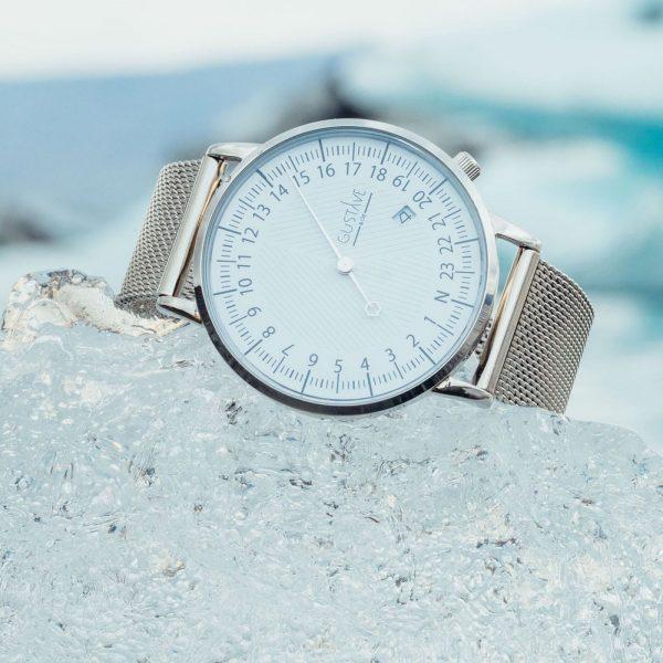 Une montre 24h est posée sur de la glace pilée, elle a un cadran blanc et le bracelet est milanais argenté pour le petit je ne sais quoi